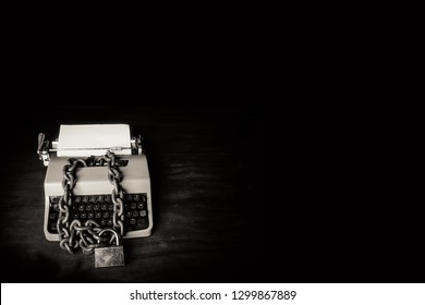 Information censorship concept - Typewriter locked with a chain and padlock on a black background