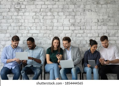 Information chain. Group of diverse multiethnic young people sitting on chairs by pairs holding gadgets exchanging data in social media, showing watching video, dropping downloading files