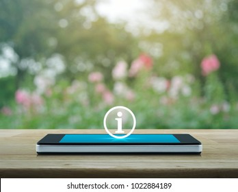 Information sign icon on modern smart phone screen on wooden table over blur pink flower and tree, Business communication concept