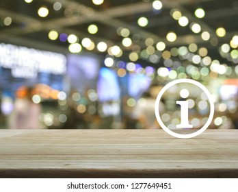 Information sign icon on wooden table over blur light and shadow of shopping mall, Business customer service and support concept