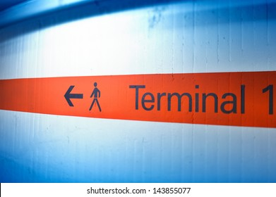 Informational sign on red stripe showing terminal number (one) at international airport