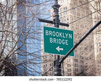 informative poster, indicator of the direction of the Brooklyn Bridge, in the area of Central Park, New York, USA. Trees and Buildings at the bottom of the poster