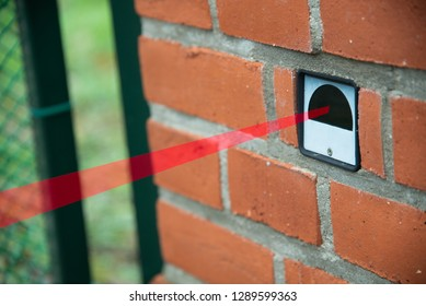 An infrared detector which is embedded in a brick wall at a gate and in which the infrared beam was graphically simulated.