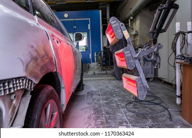 Infrared drying of car body parts after applying putty and paint on a white off-road vehicle in the body repair shop with red lanterns in the working environment