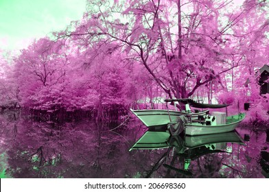 Infrared edited image of reflection floating boat and trees at the river bank