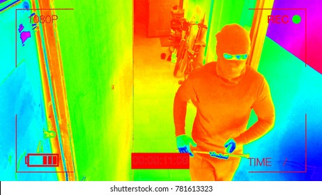 infrared hidden camera night vision recorded as the robber in a mask with a crowbar.