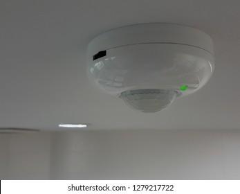infrared motion sensor on the ceiling white.