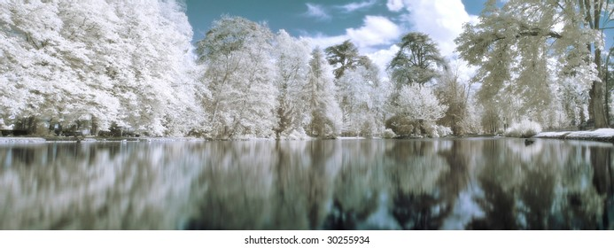 Infrared panoramic  landscape with trees reflecting in lake orton effect