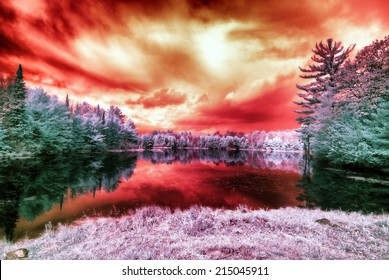 An infrared photo of an alien like landscape of a lake surrounded by trees with a blood red sky.  Photographed with a 665nm infrared converted camera.  Lightly diffused