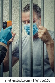 An infrared thermometer is pointed to a prisoner's forehead. A middle-aged man in mask stands behind bars of the cell