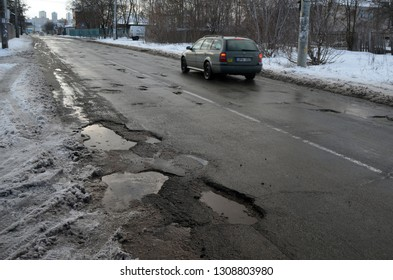 Infrastructure degradation. Poor condition of the road surface. Winter season. Hole in the asphalt, risk of movement by car, dangerous road. February 7, 2019. Saburb of Kiev,Ukraine
