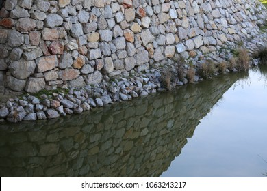 Infrastructure made of heavy stone rocks to protect a river bank. Erosion control system against water flows. Close up outdoor view of the blocks pattern and its reflection. Architecture image.