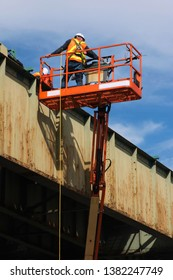 Infrastructure maintenance worker with safety harness working on a city elevated rail system in a boom lift or cherry picker.