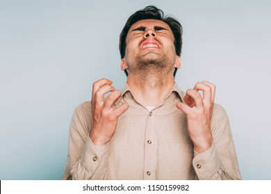 infuriated rage and anger. man went berserk with fury. portrait of a young brunet guy on light background. emotion facial expression. feelings and people reaction concept.