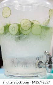 Infused cucumber water looking through the glass with moisture drops on the outside vertical and container with water spigot