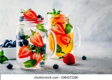 Infused detox water with blueberry, strawberry, orange and mint. Ice cold summer cocktail or lemonade in glass mason jar