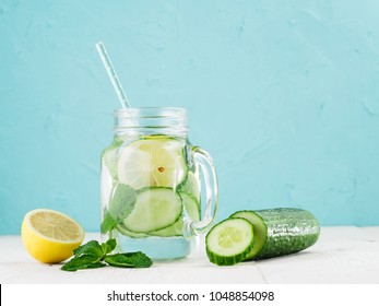 Infused detox water with cucumber, lemon and mint in glass bottle on white table. Diet, healthy eating, weight loss concept. Copy space