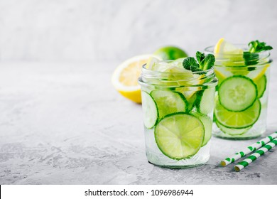 Infused detox water with  cucumber, lemon and lime. Refreshing ice cold summer cocktail or lemonade in glass jar