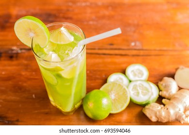 Infused detox water with Cucumber, Lime, Ginger Juice, and fresh Coriander for diet healthy eating and weight loss on a wooden table. Selective focus and toned image. Copy space.