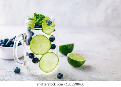 Infused detox water with green lime slices and blueberry. Iced cold summer cocktail or lemonade in glass mason jar