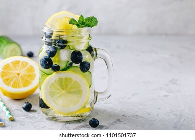 Infused detox water with lemon and cucumber slices, blueberry and mint. Ice cold summer cocktail or lemonade in glass mason jar