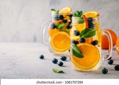 Infused detox water with orange, blueberry and mint. Ice cold summer cocktail or lemonade in glass mason jar