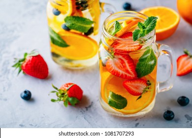 Infused detox water with orange, strawberry, blueberry and mint. Ice cold summer cocktail or lemonade in glass mason jar