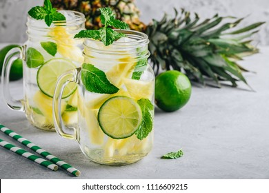 Infused detox water with pineapple, lime and mint. Ice cold summer cocktail or lemonade in glass mason jar