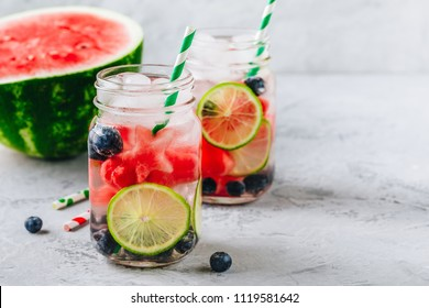 Infused detox water with watermelon, lime and blueberry. Ice cold summer cocktail or lemonade in glass mason jar