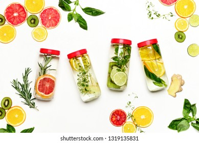Infused water in bottles with various ingredients such as culinary aromatic herbs and fruits, healthy lifestyle concept, overhead view