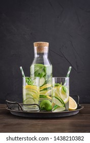 Infused water with cucumber, lemon, lime and basil in glass on tray on black background