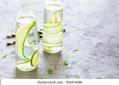 Infused water with cucumber lime and mint in bottles with black and white straws. On top of a grey concrete background. Side view copy space.