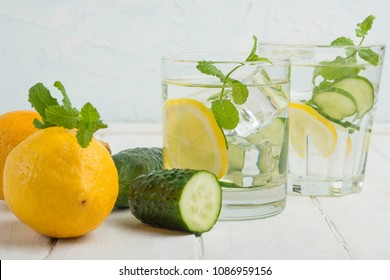 Infused water detoxification with cucumber, lemon and mint in the glass on a white table. Diet, healthy diet, the concept of weight loss.