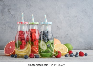 Infused water with fresh fruits, vegetables and berry in bottles on gray background