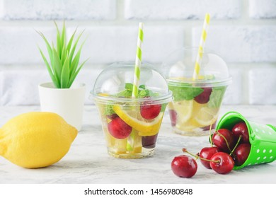Infused Water with Fresh Organic Fruit Berry Mint. Healthy Eating, Drinking. Vegetarian Diet and Detox Concept. Cup of Lemonade on White Brick Wall Background. Slimming Juicy Beverage