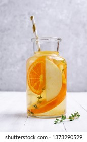 Infused water with fruit and thyme in glass on wooden background. Selective focus.