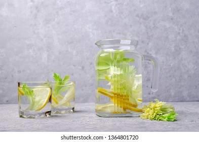 Infused water with lemon and celery in glass on grey background. Selective focus.