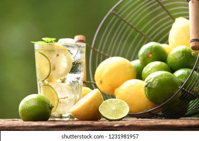 Infused water with lime and lemon in glass on wood and nature background