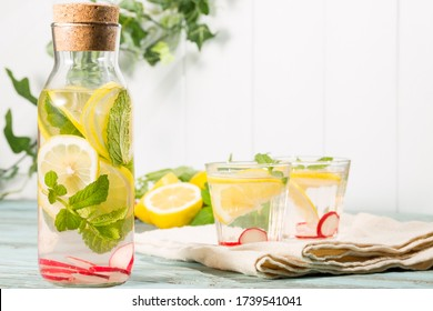 Infused-water and Carafe with lemon, spearmint and radish on wooden back ground