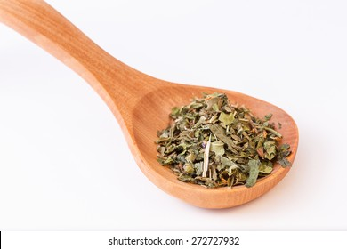 Infusion leaves in wooden spoon, spoon diagonally. Closeup on leaves