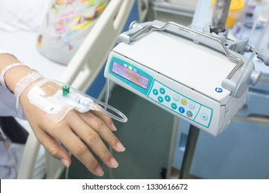 An infusion pump with a tube connecting to the catheter of a hospital patient's wrist