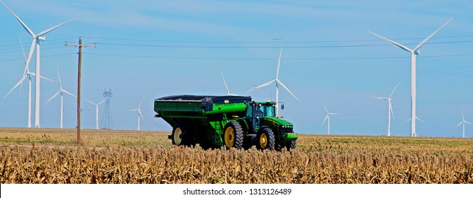 Ingalls, Kansas, USA, October 23, 2014 A John Deere combine sends its load of harvested milo grain from it's storage hopper thru it's discharge tube into the bed of a waiting tractor trailer hauler