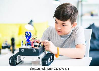 Ingenious concentrated schoolboy constructing his robotic device while preparing his engineering project