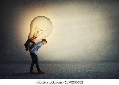 Ingenious student guy carrying a big light bulb on his back. Overloaded businessman needs a brilliant idea for solving a difficult task. Success achieving concept.