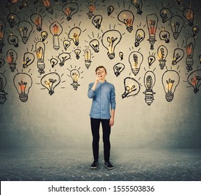 Ingenious teenage boy seeking for brilliant ideas as looks curious through the magnifying glass. Student boy try to find solutions to every problem as lots of light bulbs surrounds him.