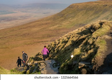 24 February 2019, Ingleborough Mountain, North Yorkshire, Uk, A small group of hill walkers and hikers are beginning their descent from Ingleborough in North Yorkshire on a hot day in february.