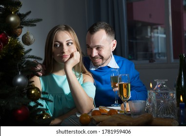 Ingratiating smiling man apologizing to girlfriend, pretending that she is offended while sitting at home table at Christmas night
