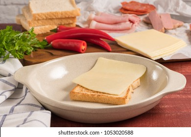 Ingredientes preparations of traditional Portuguese snack food. Francesinha sandwich of bread, cheese, pork, ham, sausages. On table.