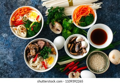 Ingredients of asian cuisine udon noodles bowl eggs vegetables spices soy sauce herbs. Flat lay top view