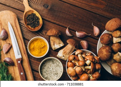 Ingredients for autumn dinner: porcini mushrooms, boletus or boletaceae mushrooms, salt, garlic and spices, knife, cutting board on rustic wooden kitchen table, top view